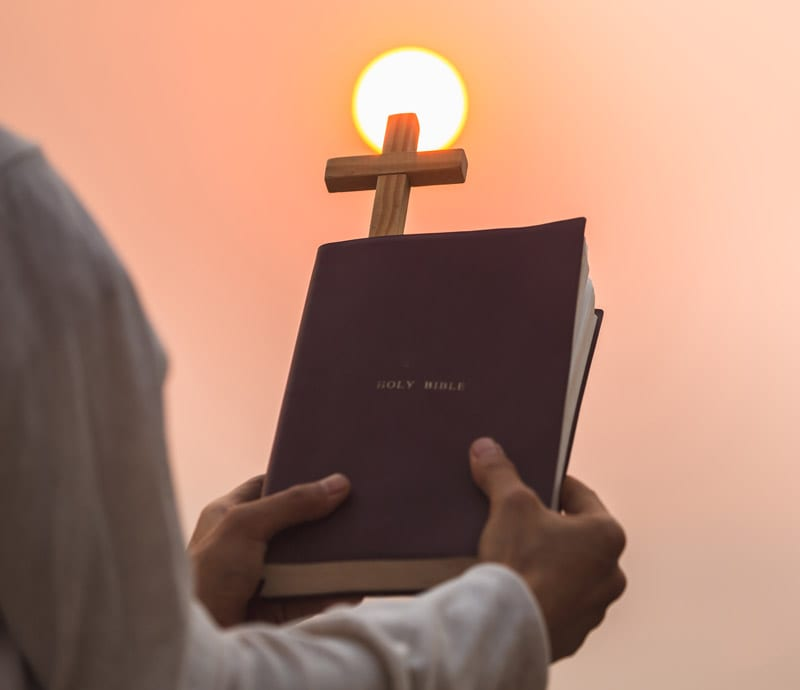 man holding holy bible in sunset with cross silo darker from sun light
